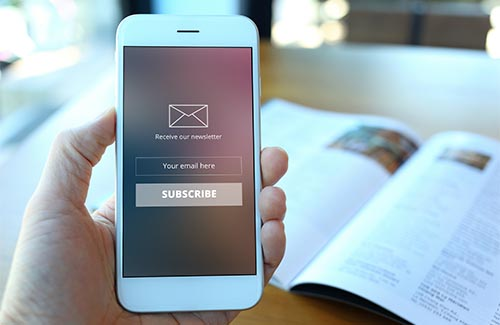 Hand holding smartphone with receive newsletter form screen on c